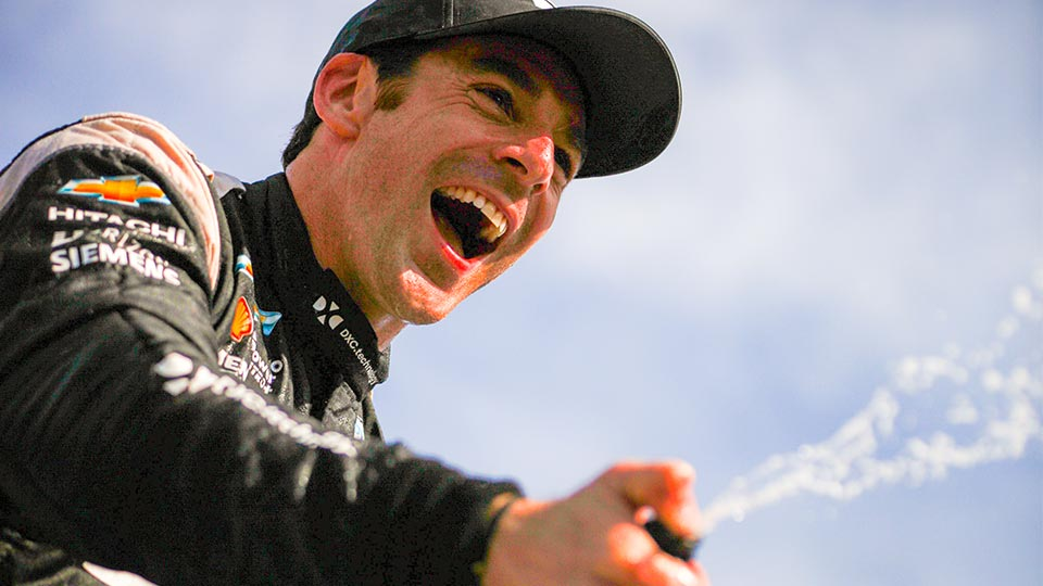 Simon Pagenaud celebrates with Champagne after his win at the Honda Indy Toronto