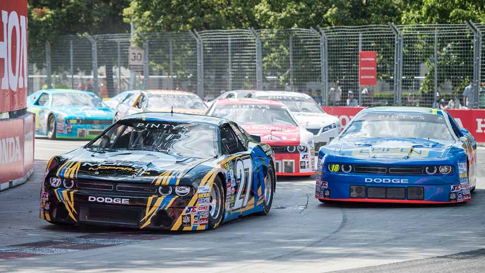 Stock cars speeding through the Honda Indy Toronto track