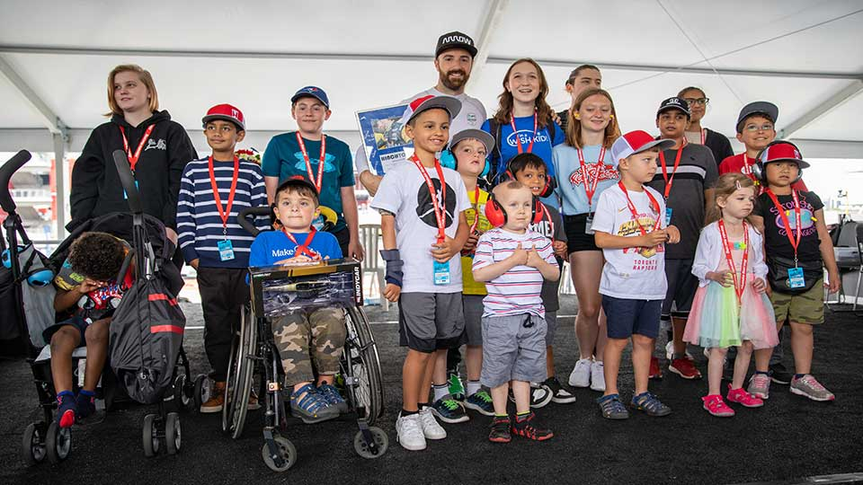 James Hinchcliffe poses takes a photo with kids from the Make-A-Wish Foundation