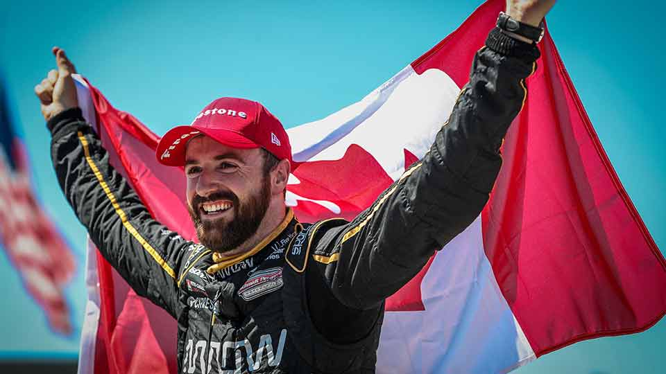 James Hinchcliffe holds the Canadian Flag
