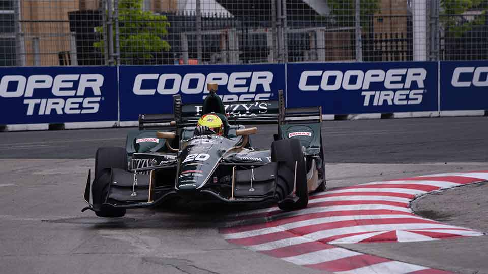IndyCar on track with Cooper Tires signage in the background
